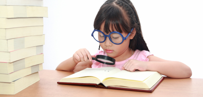 A young girl of Asian descent studies a book with a magnifying glass. She's wearing comically large glasses.