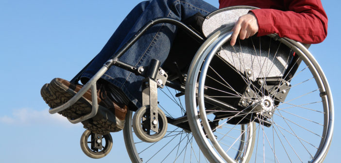 image of a manual wheelchair user popping a wheelie